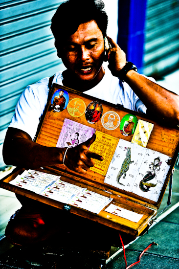 Handicapped Salesman On Wheeled Board - Bangkok, Thailand by Brett Howard Sproul. Giclee print of a handicapped salesman on a wheeled board, an original photo taken by Brett Howard Sproul.