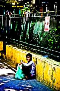 Lady Sitting Beside Fence - Hanoi, Vietnam. Giclee print of a lady sitting beside a decaying fence in Hanoi, Vietnam, an original photo taken by Brett Howard Sproul.