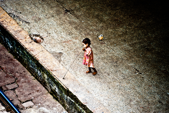Young Girl With Bamboo Stick (beside railroad tracks) - Yangon, Burma