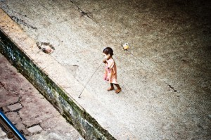 Young Girl With Bamboo Stick (beside railroad tracks) - Yangon, Burma. Giclee print of a young girl playing with a bamboo stick along the railroad tracks in Burma, an original photo taken by Brett Howard Sproul.