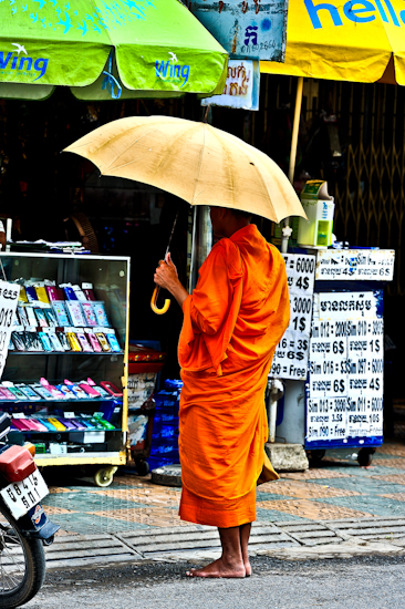 Monk In Street Awaiting Alms - Phnom Penh, Cambodia by Brett Howard Sproul.